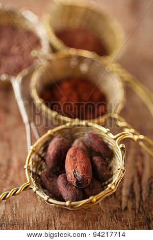 cocoa beans in old rustic style silver sieves on old wooden background