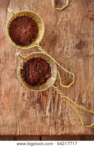 cocoa powder  in old rustic style silver sieves on old wooden background