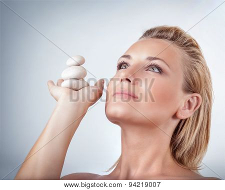 Portrait of beautiful woman holding on hand spa stones over gray background, natural cosmetics and treatment, zen balance