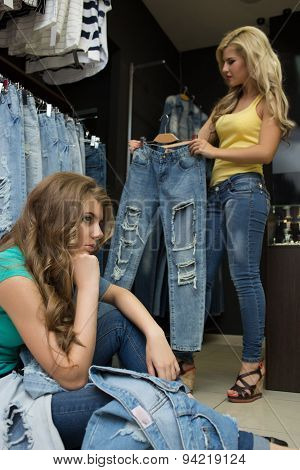 Two girls buy jeans in the store. tired girlfriend