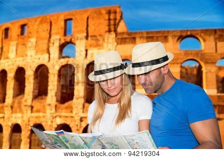 Beautiful young couple standing near Coliseum and looking in the map, searching right direction to next sightseeing, active summer vacation in Rome, Italy, Europe