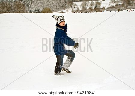 Child Has A Big Snowball For The Snowman In His Hand