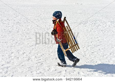Boy Is Carrying His Sledge