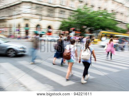 People Crossing The Street On The Zebra Crossing