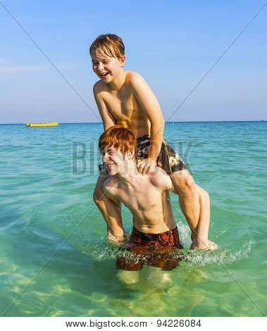 Brothers Are Enjoying The Clear Warm Water In The Ocean And Play Pickaback