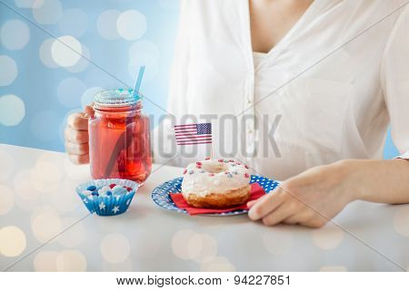 independence day celebration, patriotism and holidays concept - close up of woman eating glazed donut, drinking juice from glass mason jar mug and celebrating 4th july over blue lights background