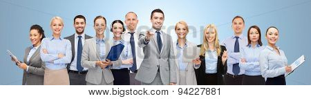 business, people, corporate, teamwork and office concept - group of happy businesspeople pointing at you over blue background