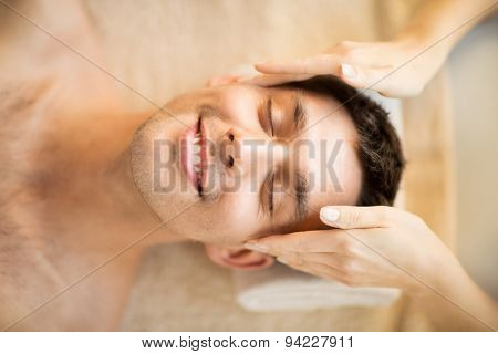close up of man face in spa salon getting facial massage