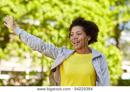 people, race, ethnicity and gesture concept - happy african american young woman waving hand in summer park