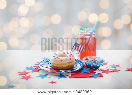 american independence day, celebration, patriotism and holidays concept - close up of glazed sweet donut with flag and candies in disposable tableware at 4th july party over lights background