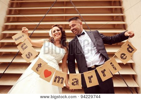Bride And Groom Holding Just Married Signs