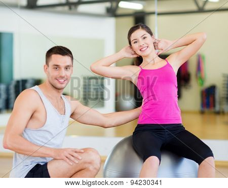 fitness, sport, training, gym and lifestyle concept - male trainer with woman doing crunches on the ball