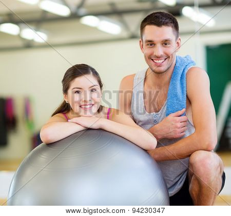 fitness, sport, training, gym and lifestyle concept - two smiling people with fitness ball in the gym