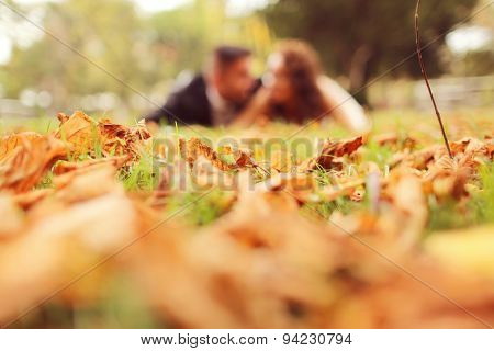 Bride And Groom Laying On Autumn Leaves