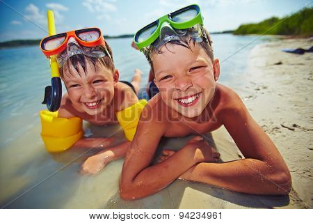 Happy siblings in goggles looking at camera on the beach