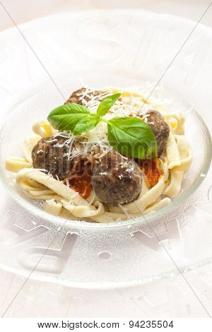 homemade tagliatelle with meatballs in tomato sauce