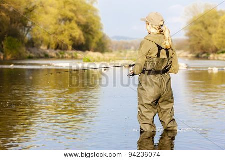 woman fishing in the river in spring