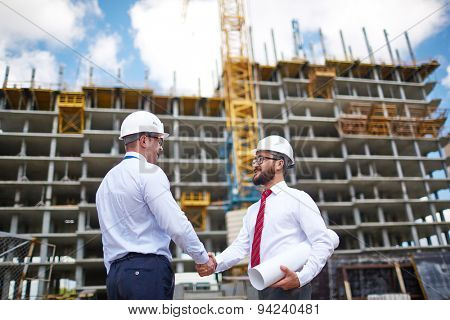 Two architects handshaking on background of building structure