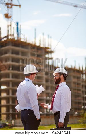 Male architects in helmets and formalwear talking near unfinished construction