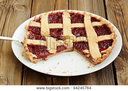 Old Fashioned Lattice Flan With Strawberry Jam Cut With Metal Spatula On Wooden Background