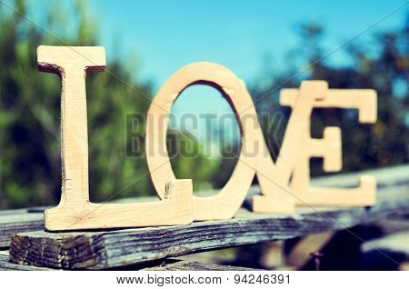 closeup of wooden letters forming the word love on an old wooden lath in a rustic scenery outdoors