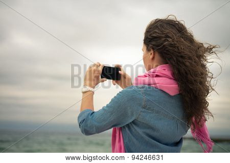 Young Woman In A Denim Dress With A Pink Scarf Takes A Picture Of The Sea
