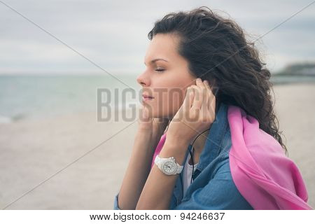 Young Woman With Closed Eyes Listening To Music With Headphones On The Beach