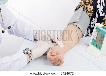 Doctor Checking Pulse Of Patient With Stethoscope  On Table Isolated White Background.