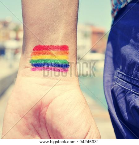 closeup of a young man seen from behind with a rainbow flag painted in his wrist