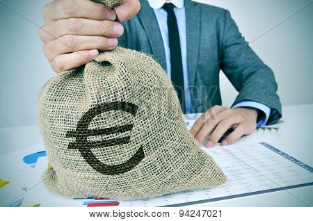 a young man wearing a gray suit seated at an office desk full of charts and financial balances holds a burlap money bag with the euro currency sign in his hand