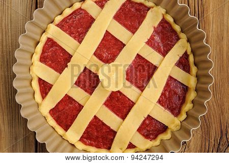Raw Lattice Round Cake With Strawberry Jam In Metal Form On Wooden Background