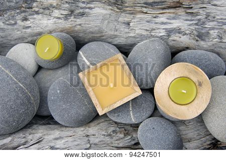 Three candle with set of stones on driftwood