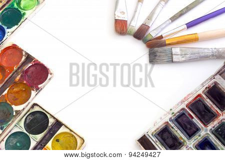The Layout Of The Paints And Brushes Isolated Over White