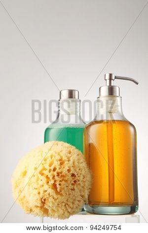 cleanser and shampoo in the glass container with natural bath sponge
