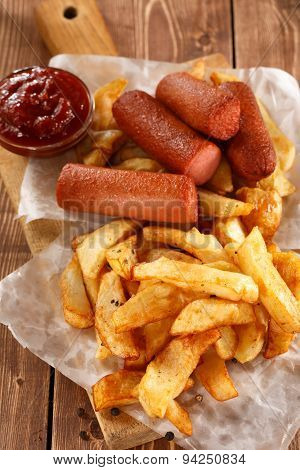 Fried Potatoes and grilled sausage on wooden board