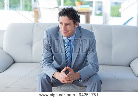 Thoughtful businessman looking away on couch in living room