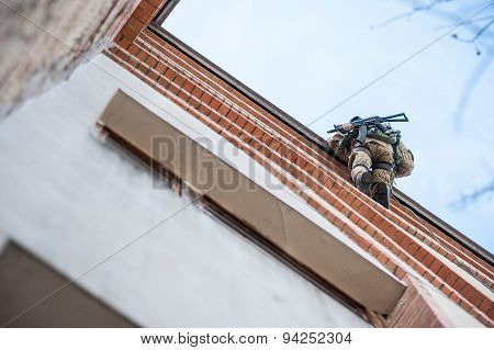 Armed soldiers climb to the roof