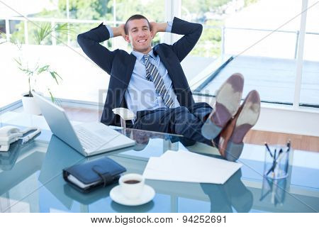Businessman relaxing in a swivel chair in his office