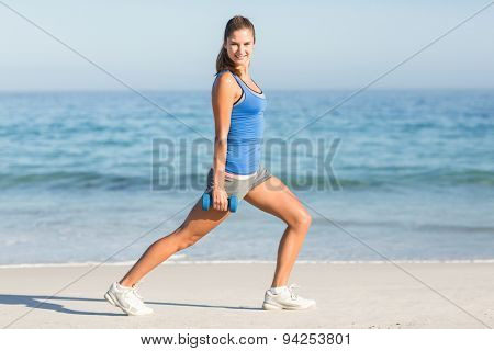 Beautiful fit woman stretching with dumbbells at the beach