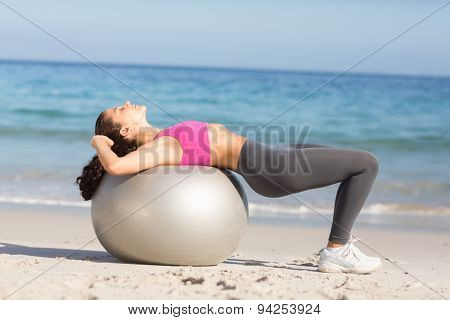 Fit woman stretching on exercise ball at the beach