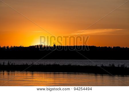 Sunset behind lake and forest