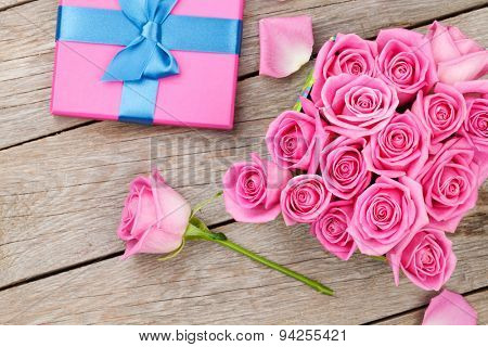 Valentines day with gift box full of pink roses over wooden table. Top view