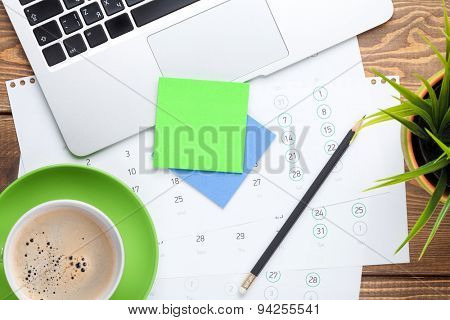 Office desk table with computer, supplies, flower and coffee cup. Top view