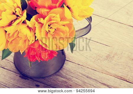 Colorful tulips bouquet in watering can on wooden table. Top view with copy space. Retro toned
