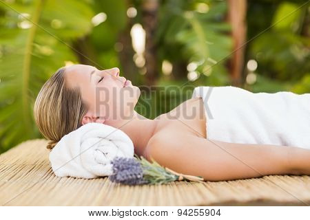 Peaceful blonde lying on bamboo mat with flowers at the health spa