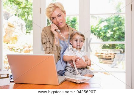 Pretty blonde woman with his son phoning and using laptop in the office