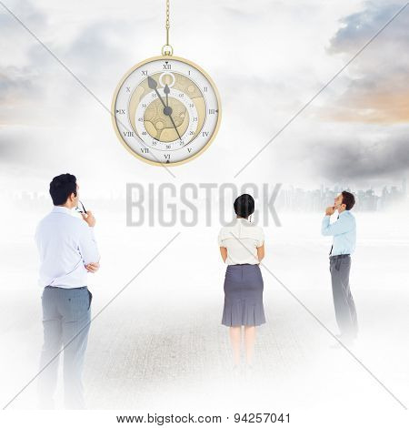 Thoughtful businessman with hand on chin against large city on the horizon
