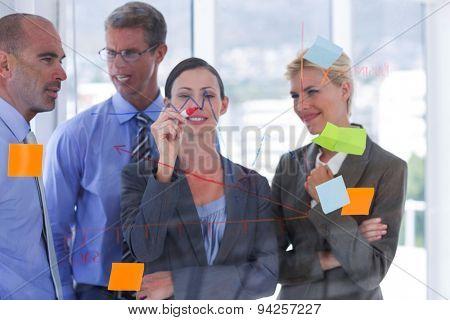 Businesswoman drawing graph on the board in the office