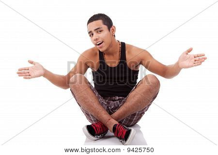 Young Man With Open Arms, Sitting On Floor, Isolated On White, Studio Shot