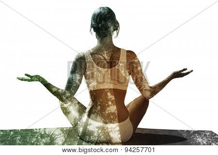Fit woman sitting in lotus pose against low angle view of tall trees